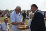 Wicemarszałek Grzegorz Kapusta dzieli się chlebem z uczestnikami dożynek