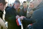 Marszałek podpisuje na pamiątkę wstęgę