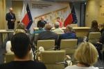 przy stole prezydialnym w tle zdjęcia Marszałek Jarosław Stawiarski i zastępca dyrektora ROPS Marta Drozd. na sali siedzą beneficjenci programu
