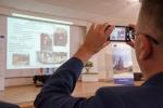 Jeden z uczestników konferencji fotografuje wystąpienie Dyrektora Jaworowskiego Parku Narodowego przy pomocy telefonu komórkowego.