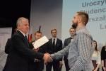 Marszałek Województwa Lubelskiego Sławomir Sosnowski wręcza stypendium naukowe.