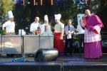 """""""Lubelskie kucharzenie"""" w wykonaniu Łukasza Gołąba z UMWL (w czerwonym fartuchu) i Tomasza Solisa – producenta i radnego Sejmiku (drugi z lewej), przyciągnęło na scenę biskupa diecezjalnego drohiczyńskiego Tadeusza Pikusa, który okazał się znakomitym znawcą kuchni wschodniej"""