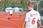 """Mecz w ramach akcji """"z podwórka na boisko"""". Zawodnik drużyny urzędników w białej koszulce, stoi plecami do obiektywu. Na koszulce logo lubelskie smakuj życie. poniżej czerwona cyfra sześć. w tle rozgrzewający się na bosiku zawodnicy urzędu."""