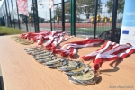 """Mecz w ramach akcji """"z podwórka na boisko"""". Pamiątkowe medale z biało-czerwonymi wstęgami leżące na stole. W tle nowe boisko."""